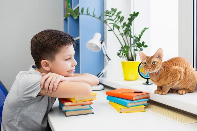 Jongen aan tafel met stapel boeken