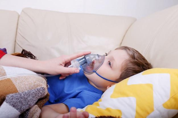 Jongen ademen door vernevelaar. ziek kind met vernevelaar voor kinderen.