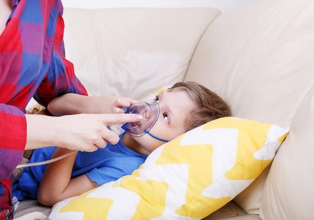 Jongen ademt door vernevelaar moeder houdt tijdens inhalatie een vernevelaarmasker in het gezicht van de jongen. ziek kind met vernevelaar voor kinderen.