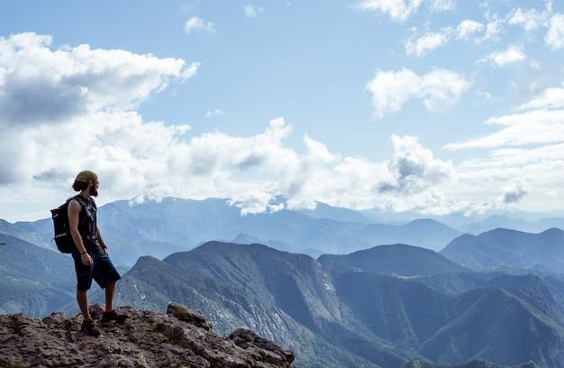 Jongen alleen op een berg die de horizon bekijkt