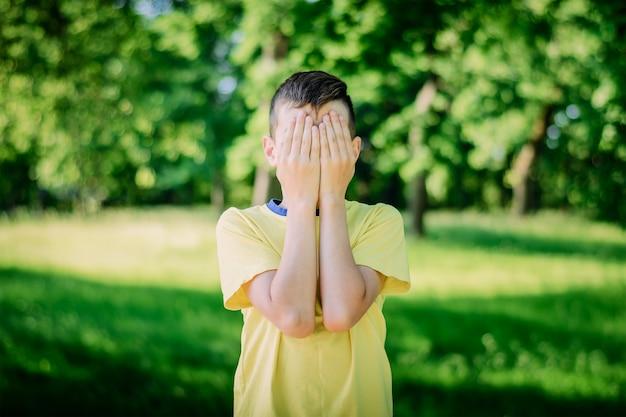 Jongen bedekt gezicht met zijn handen
