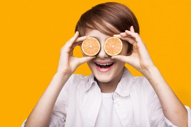 Jongen bedekt zijn oog met stukjes citroen