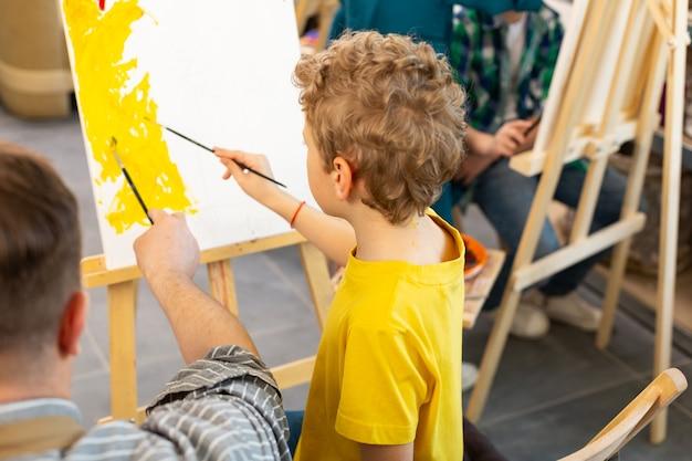 Jongen bedrijf schilderij penseel kleurend papier in de buurt van leraar