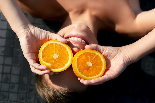 Jongen bij het zwembad met sinaasappel