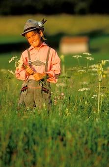Jongen bloemen plukken in het veld