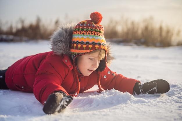 Jongen buiten spelen met eerste sneeuw