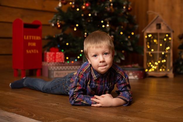 Jongen dichtbij thuis boom die voor kerstmis wordt verfraaid.