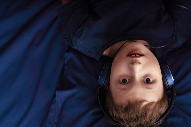 Jongen die aan muziek in hoofdtelefoons luistert liggend in bed