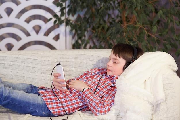 Jongen die aan muziek in hoofdtelefoons met in hand telefoon luistert.