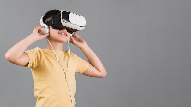 Jongen die aan muziek met virtuele werkelijkheidshoofdtelefoon luistert
