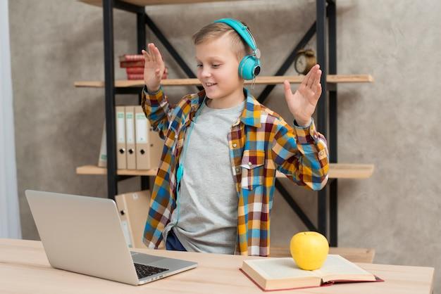 Jongen die aan muziek op laptop luistert