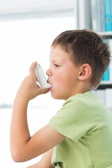 Jongen die astmainhaleertoestel in het ziekenhuis met behulp van