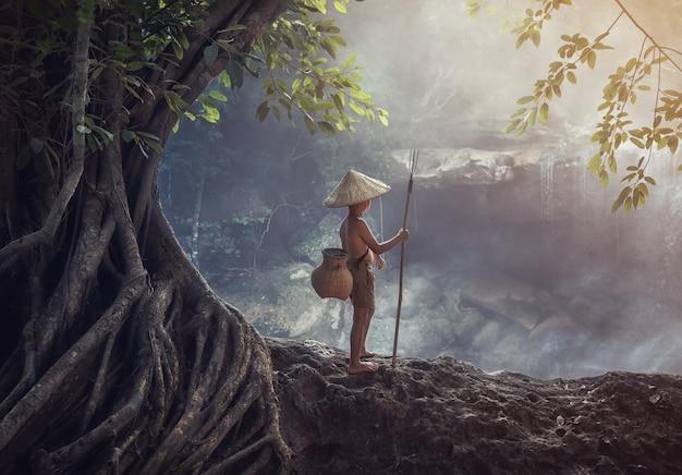 Jongen die bij de kreek, het platteland van thailand vist
