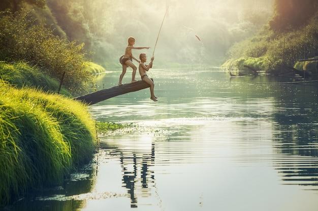 Jongen die bij de rivier, platteland van thailand vist