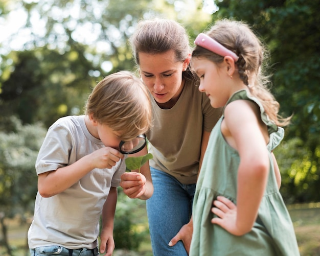 Jongen die bladeren met vergrootglas bekijkt