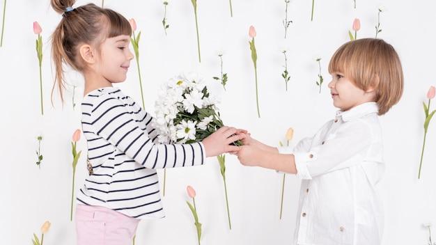 Jongen die bloemen geeft aan leuk meisje