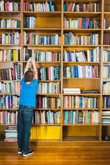 Jongen die boek van bibliotheekplank neemt