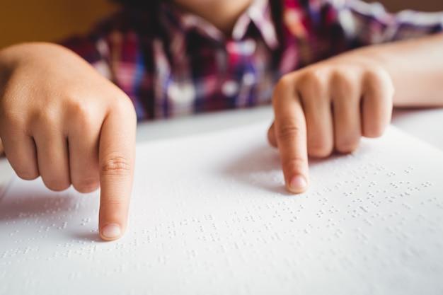 Jongen die braille gebruikt om te lezen