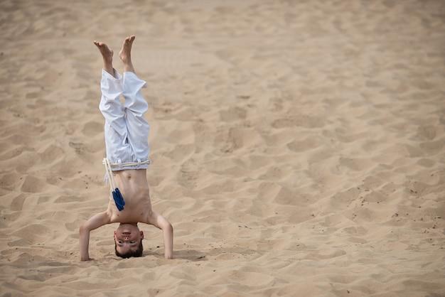 Jongen die capoeira, handstand uitoefent