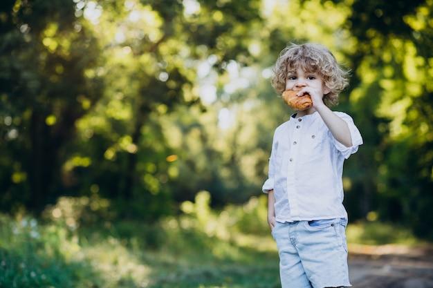 Jongen die croissant in park eet