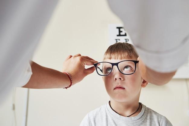 Jongen die de specificaties bekijkt. arts die het kind een nieuwe zwarte bril geeft voor zijn visie.