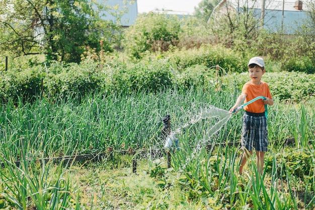 Jongen die de tuin met een slang water geeft. kinderen helpen in het dorp. planten water geven met warmte. zomervakantie bij mijn oma in het dorp. arbeidstherapie voor kinderen.