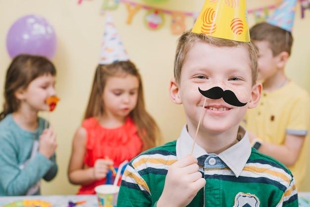 Jongen die document snor op verjaardagspartij draagt