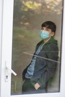 Jongen die door het raam naar buiten kijkt