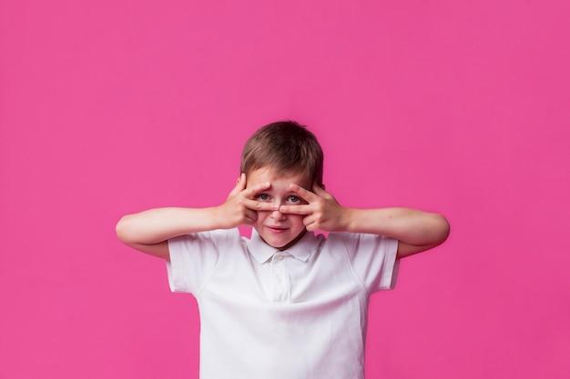 Jongen die door v-teken over roze achtergrond gluren