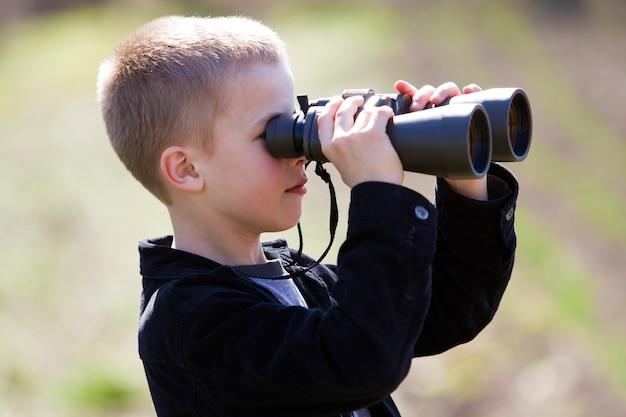 Jongen die door verrekijkers in afstand kijkt