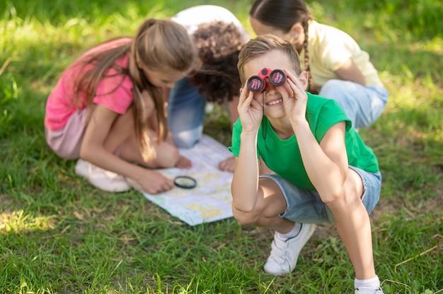 Jongen die door verrekijkers kijkt en vrienden die kaart bestuderen
