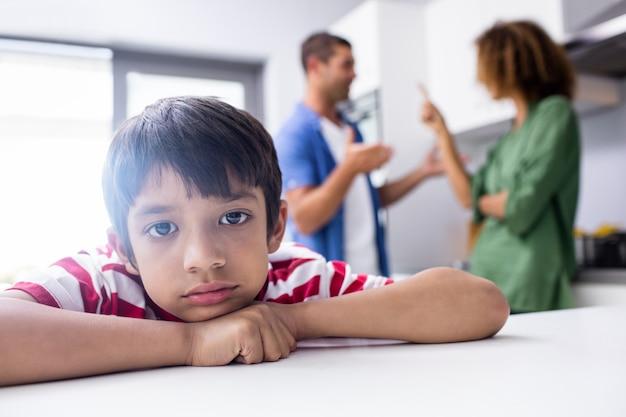 Jongen die droevig voelt terwijl zijn ouders ruzie maken