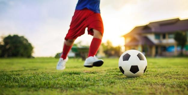 Jongen die een bal schopt tijdens het spelen van straatvoetbal op het groene grasveld om te oefenen
