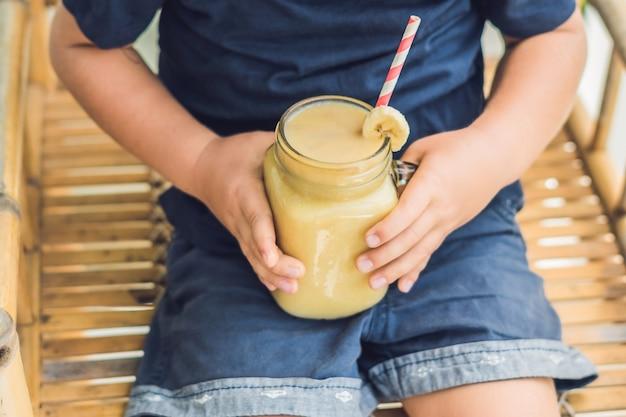 Jongen die een bananensmoothie, goed voedingsconcept houdt.