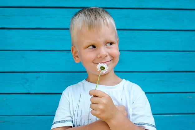 Jongen die een bloem ruikt