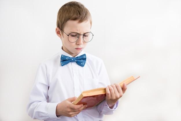 Jongen die een boek in grote glazen leest