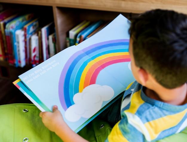Jongen die een boek leest bij een schoolbibliotheek