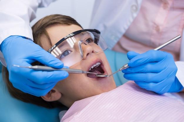 Jongen die een bril draagt die tandheelkundige behandeling neemt