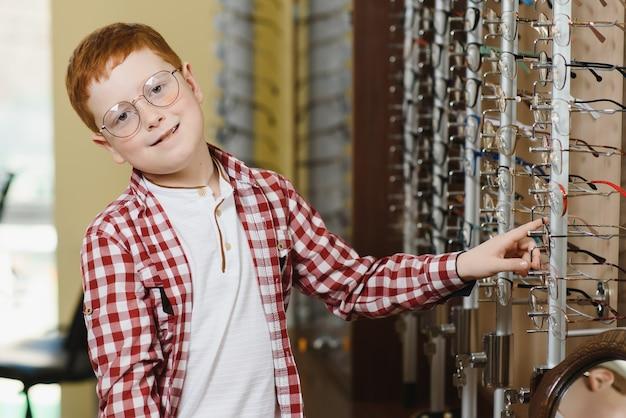 Jongen die een bril kiest bij optica-winkel.