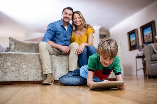Jongen die een digitale tablet gebruikt terwijl ouders die op bank zitten