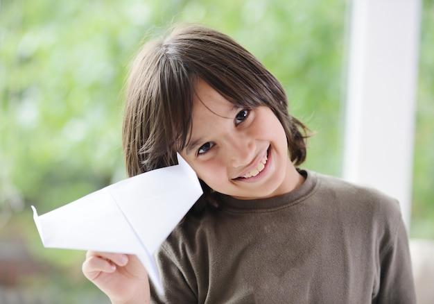 Jongen die een document vliegtuig van huisvenster vliegt