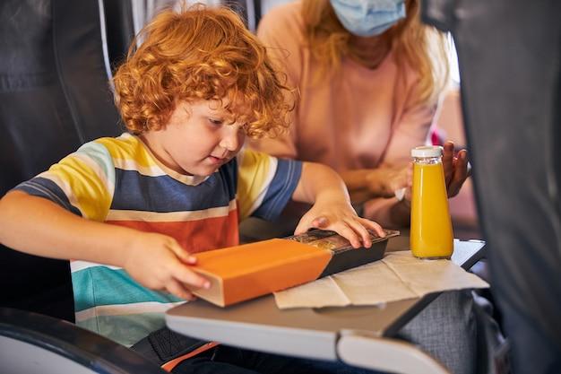 Jongen die een doos koekjes opent in een vliegtuig