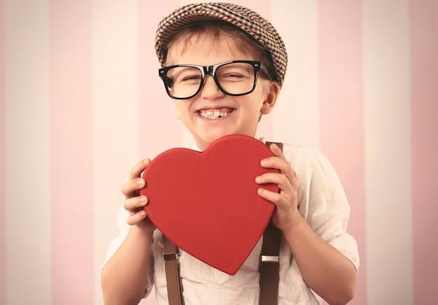 Jongen die een doos van de geheimzinnige hartvorm houdt