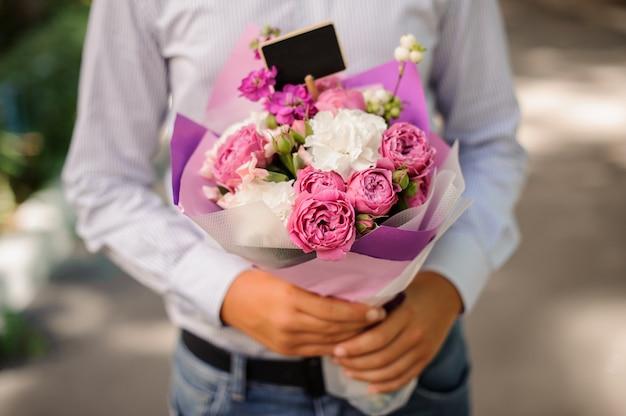Jongen die een feestelijk helder roze boeket bloemen houdt