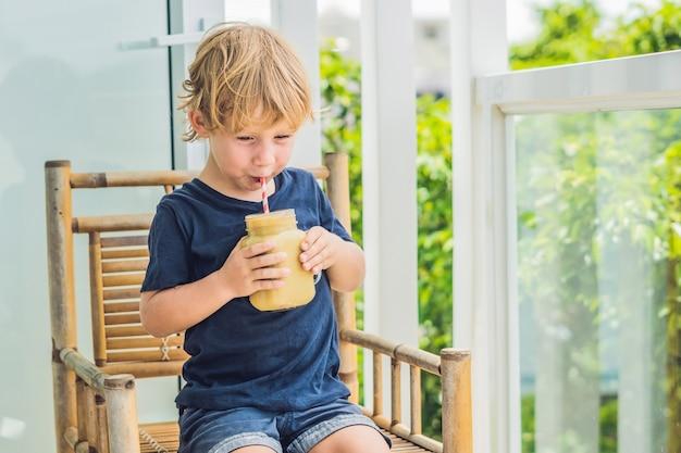 Jongen die een goed voedingsconcept van bananensmoothie houdt