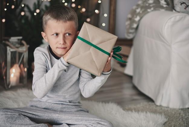 Jongen die een ingepakt cadeau schudt