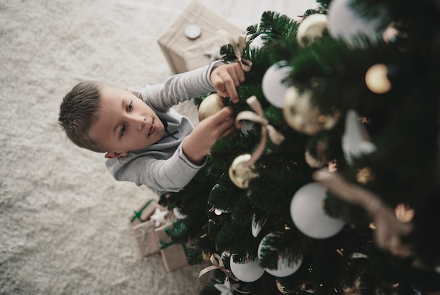 Jongen die een kerstboom verfraait