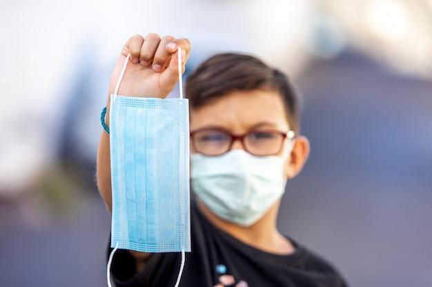 Jongen die een medisch masker, close-up houdt. stop het coronavirus. selectieve aandacht