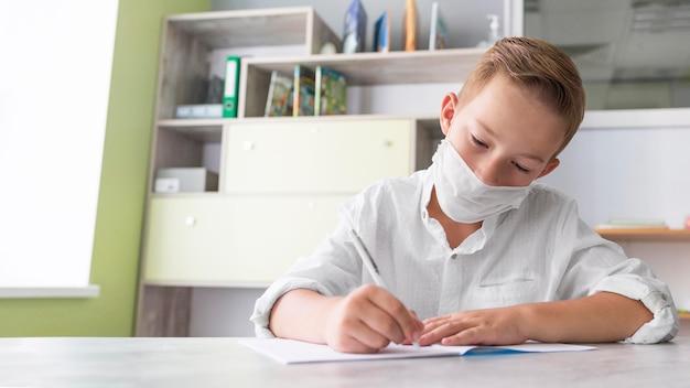 Jongen die een medisch masker draagt in de klas met een kopie ruimte