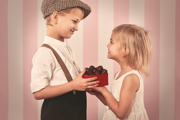 Jongen die een meisjesdoos vol chocolaatjes geeft